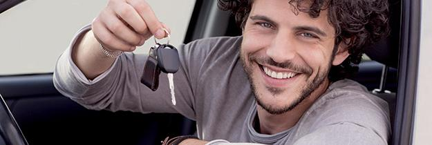 Homme donateur tendant les clés d'une voiture d'occasion cédée