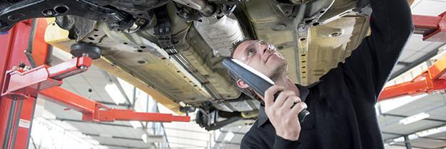 Mécanicien inspectant une voiture d'occasion montée sur un pont.