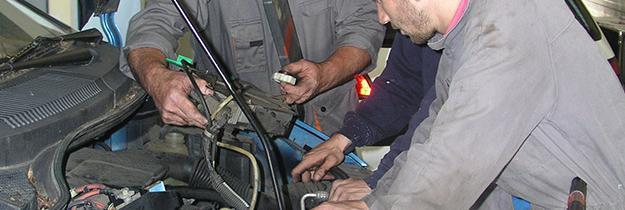 Trois mécaniciens réparant une voiture, capot ouvert.